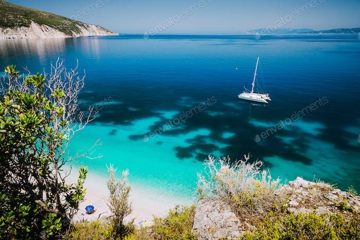 Playa de Fteri, Cefalonia, Grecia. Barco en catamarán blanco en aguas cristalinas de mar azul. Turistas
