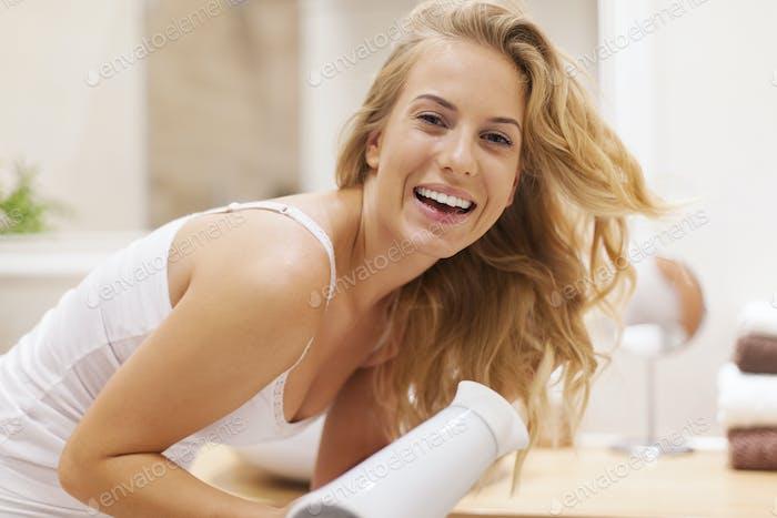 Schöne glückliche Frau Trocknen Haare im Bad