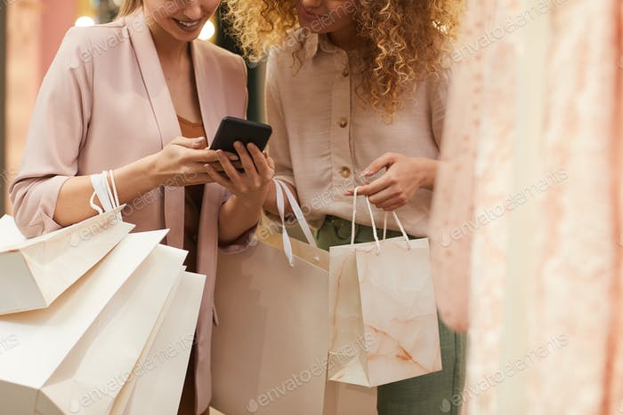 Two Young Women Using Smartphone in Boutique