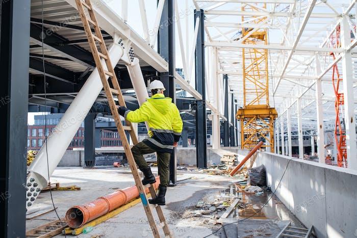 Rückansicht des Mannarbeiters im Freien auf Baustelle, Arbeiten