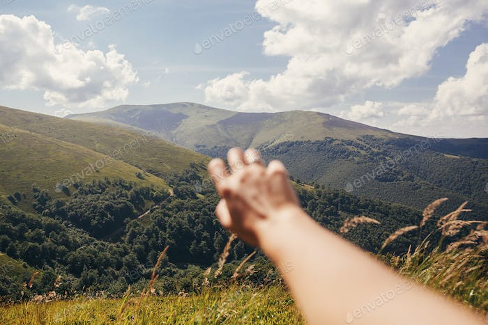 Traveler hand reaching out to mountains
