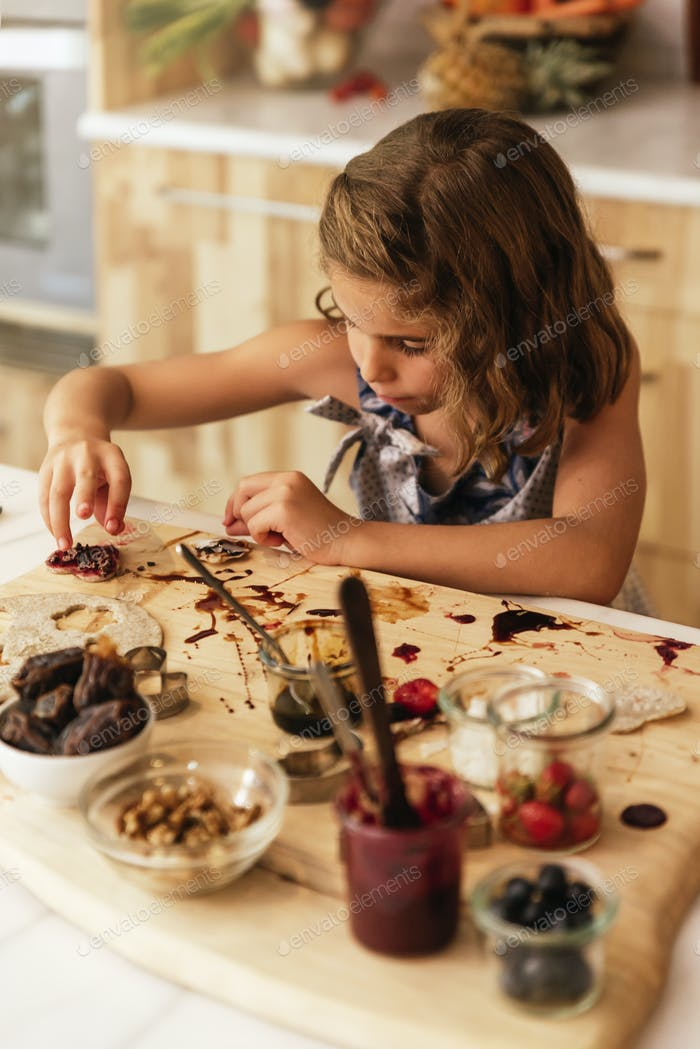 Portrait of little girl preparing baking cookies.