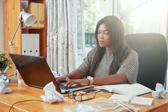 Modern black businesswoman working on laptop