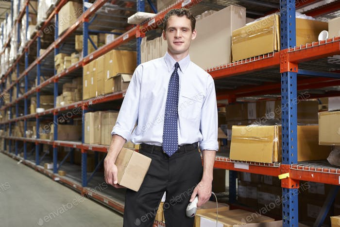 Businessman With Package And Scanner In Warehouse