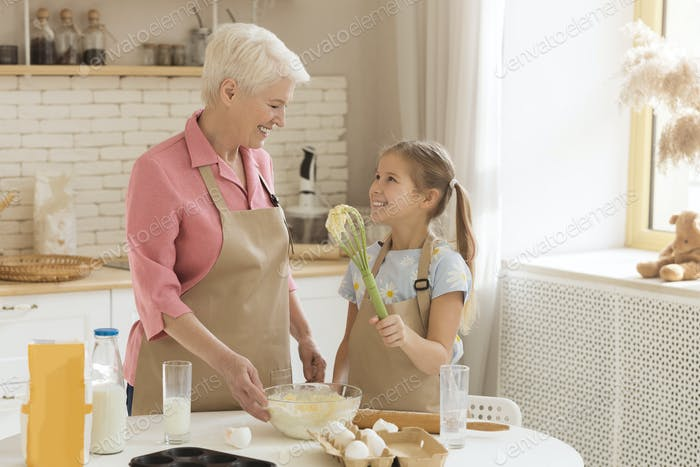 Adorable little girl helping her grandma to bake in kitchen, empty space