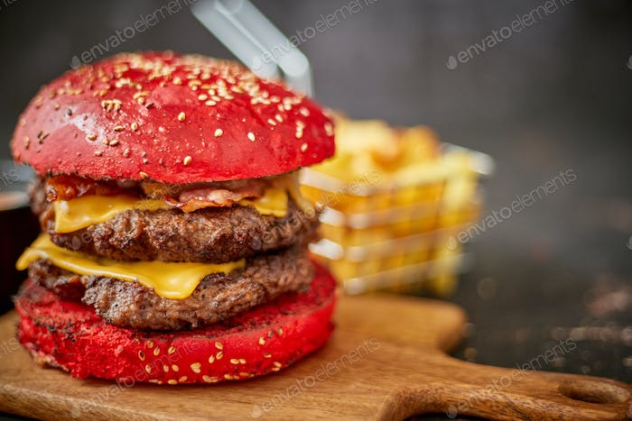 Homemade red sesame bun double bacon cheese burger. Served with french fries on wooden board