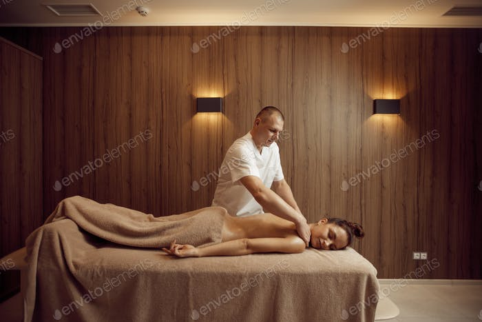 Male masseur pampering neck to young woman
