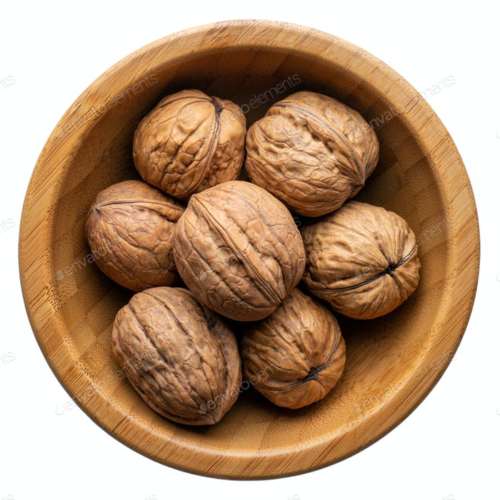 Unpeeled walnuts in a round wooden bowl