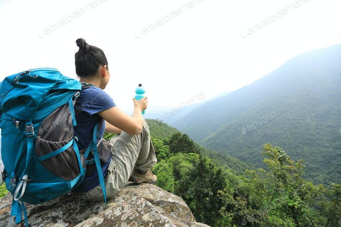 Hiker sit on mountain top cliff edge looking at the view