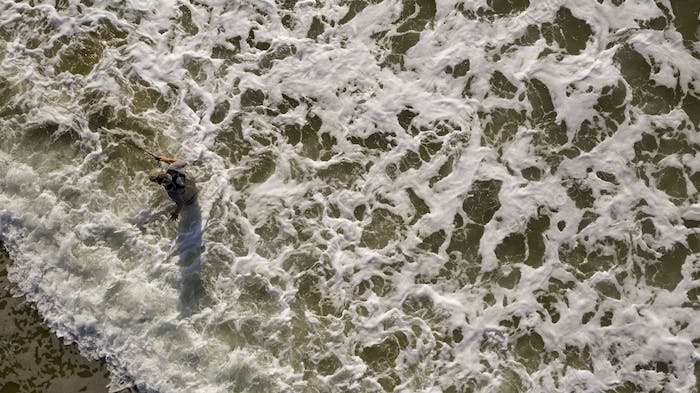 Fisherman Wades in Ocean Surf Hoping to Catch Fish