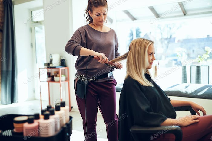 Young stylist straightening a clients hair in her salon