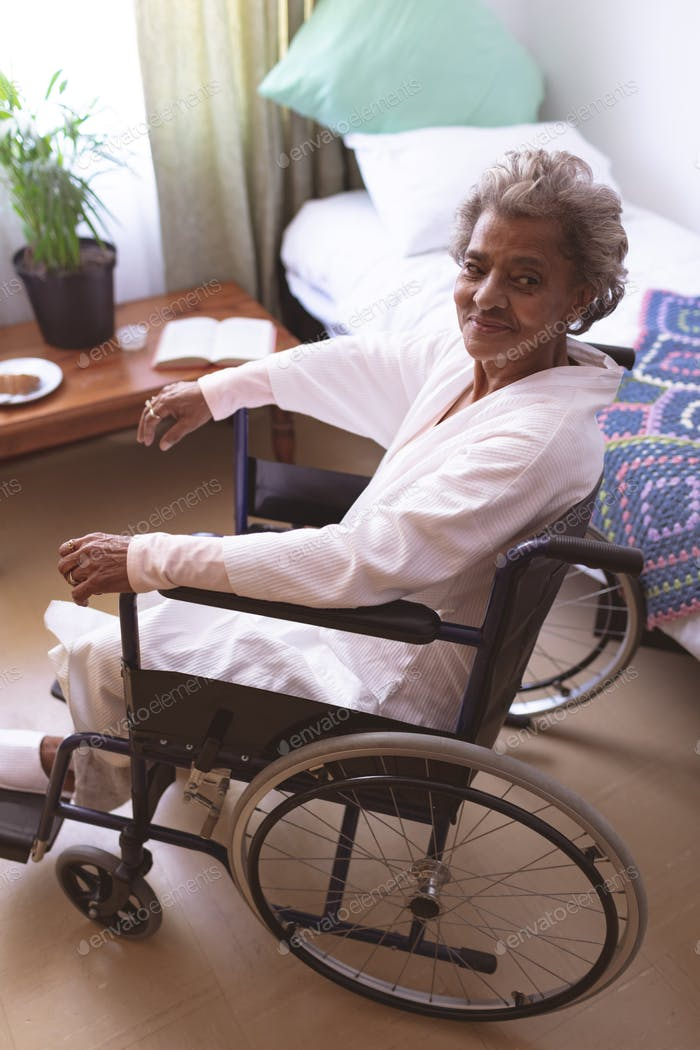 Happy senior woman sitting in wheelchair while looking at camera  at nursing home