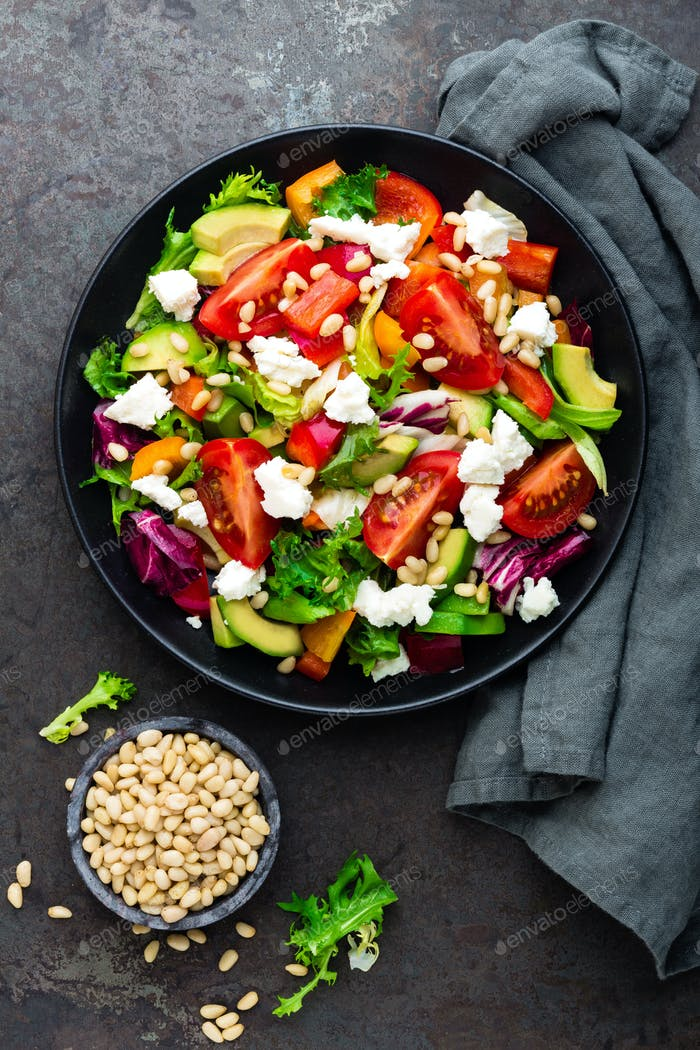 Vegetable dish, salad with avocado, pepper, tomato, italian mix, fresh lettuce, feta cheese