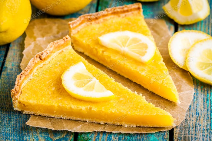 two pieces of lemon tart with slice of lemons closeup