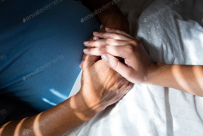 Close-up of doctors hand consoling senior patient in bedroom
