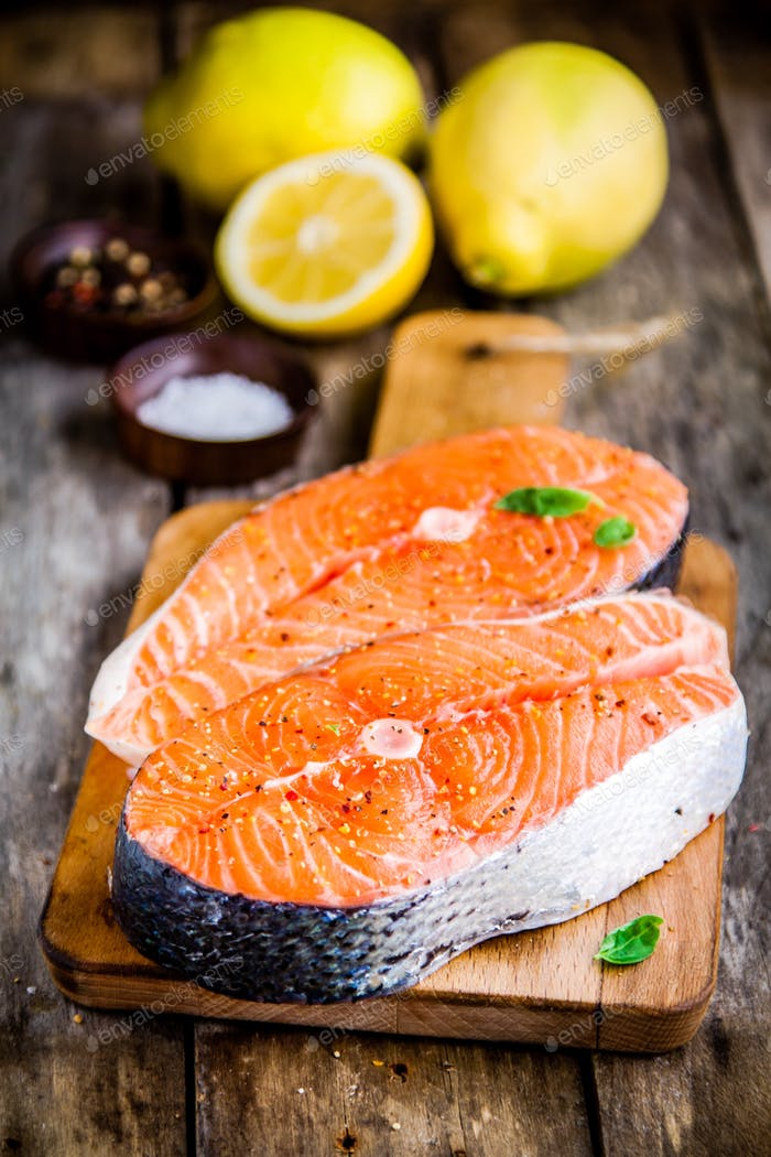 Two fresh raw salmon steaks with lemons closeup