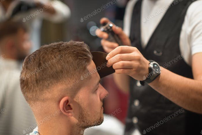 Qualified barber fixating hair of customer with hair spray