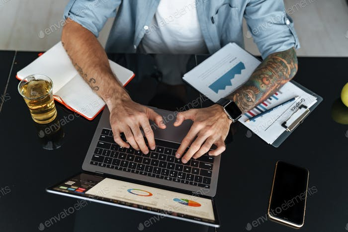 Top view of a man typing on laptop computer