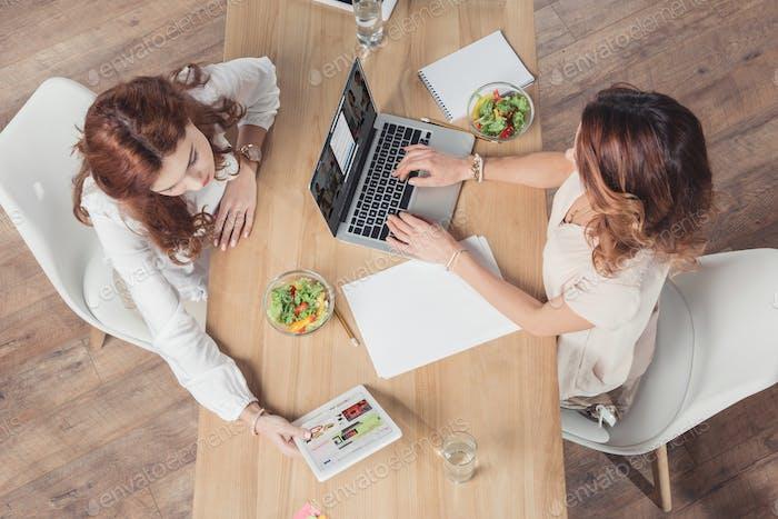 Draufsicht auf Geschäftsfrauen, die gemeinsam Salat zum Mittagessen und Networking im Büro