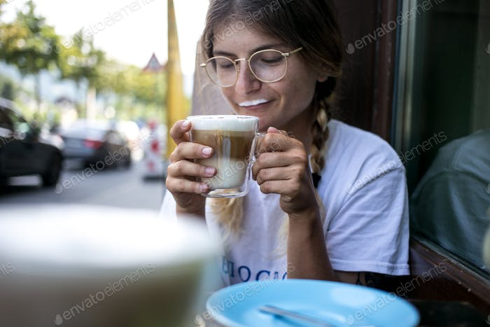 Cute millennial young pretty woman drink coffee
