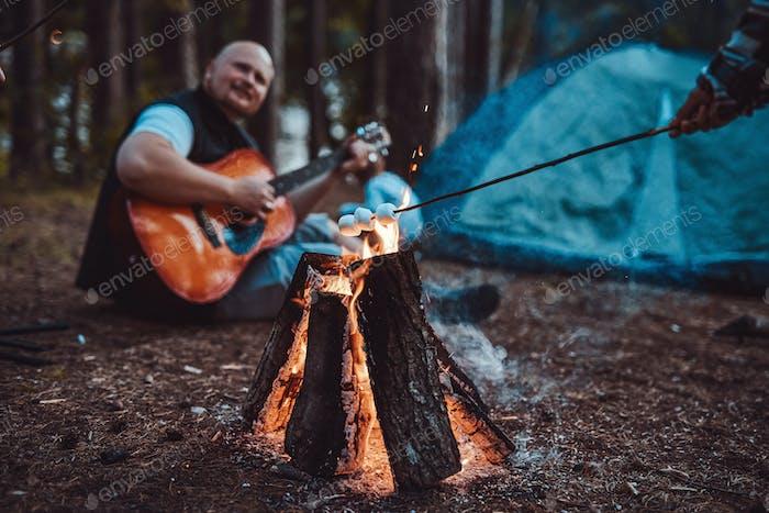 Зефир тост на костра и лысый человек играет на гитаре