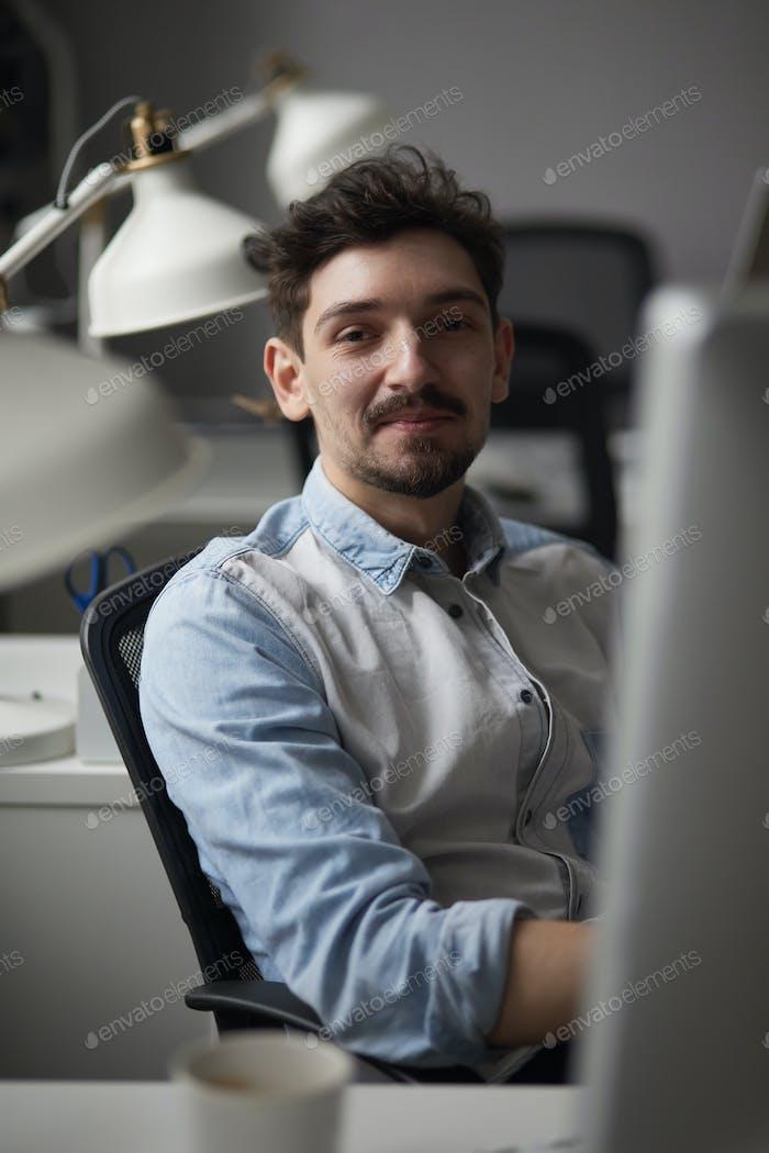 Junge intelligente Mann arbeitet in modernen Loft-Studio-Büro mit