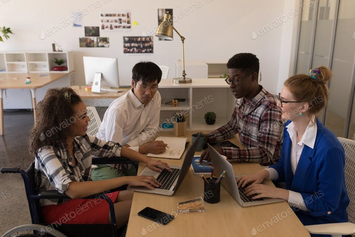 Side view of young diverse business executives interacting with each other in modern office