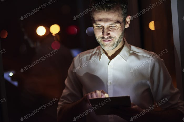 Mature men using a tablet at night