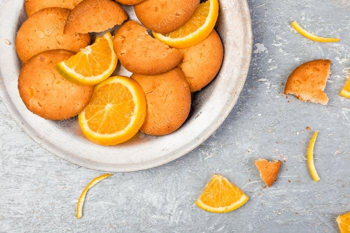 Kekse und orangefarbene Zitrusfrüchte auf Metallplatte auf grauem Hintergrund. Flache Lag