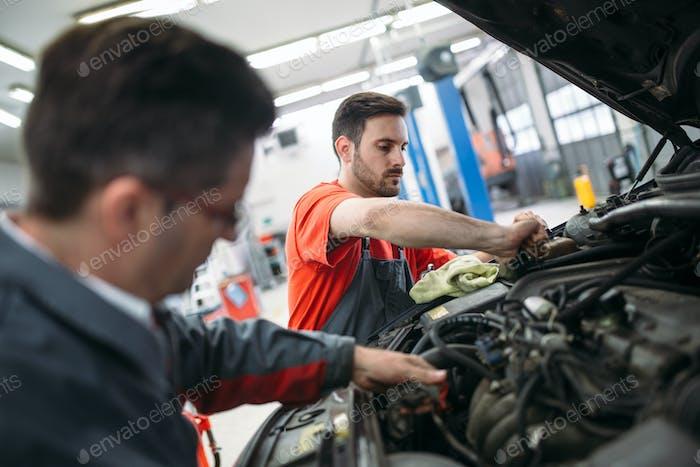 Profecional car mechanic changing motor oil at maintenance repair service station