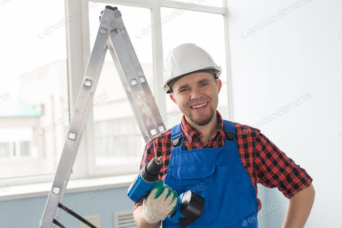 Man with screw gun or screwdriver, Building master, carpenter working with drilling machine