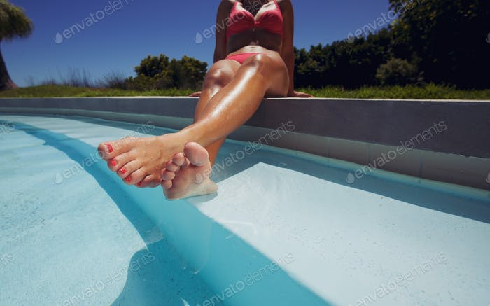 Female model in bikini relaxing by swimming pool