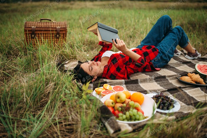 Woman reads book, picnic on meadow