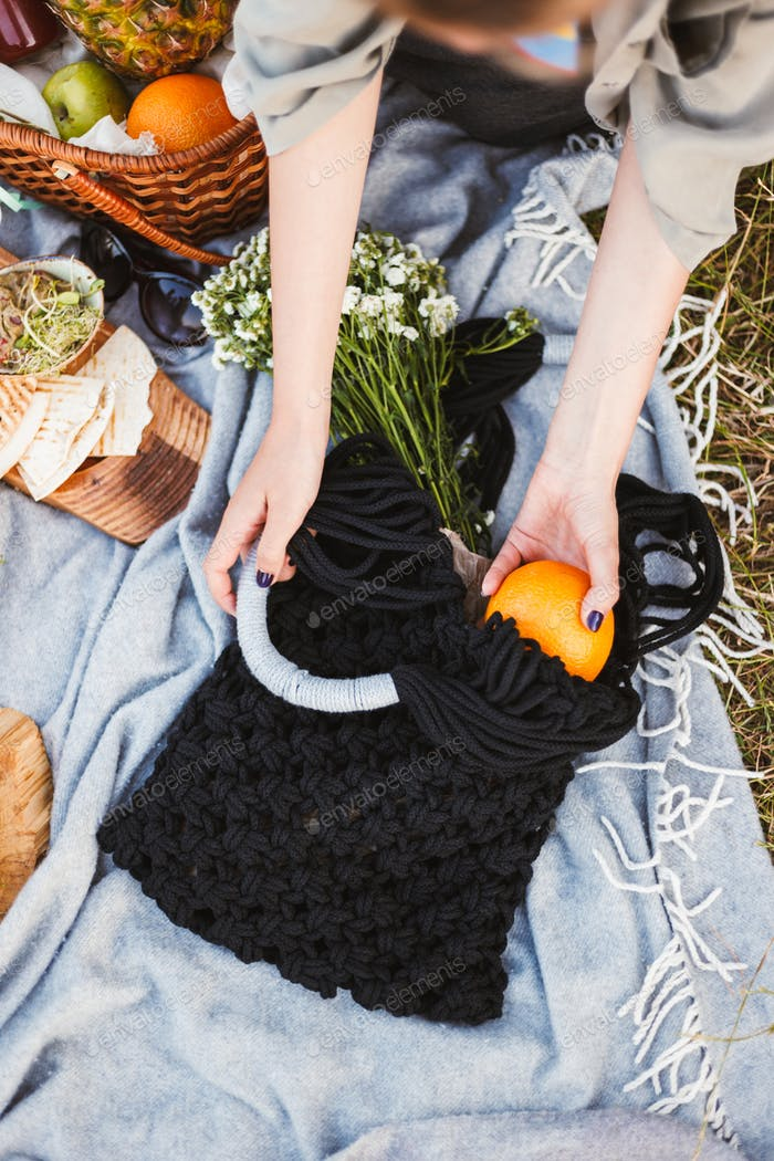 Close up photo of woman hand holding orange and bag with wildflo