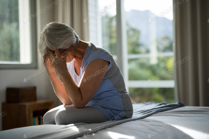 Tense senior woman sitting on bed in bedroom