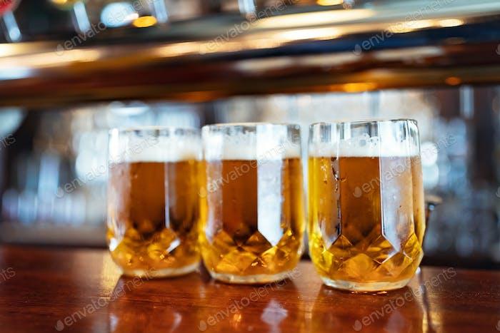 Бокалы светлого пива на прилавке паба