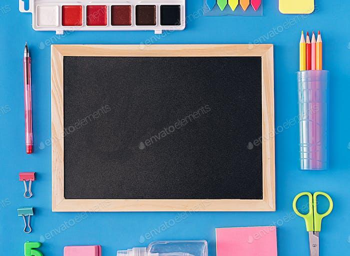 Around school chalkboard school supplies on blue background