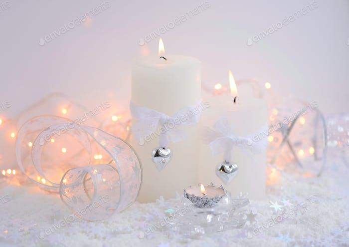 Christmas candles on the snow and Christmas lights. Festive Chri