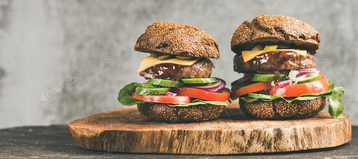 Beef meat cheeseburgers with barbeque sauce on board, wide composition