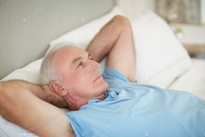 Thoughtful senior man lying on bed in bedroom