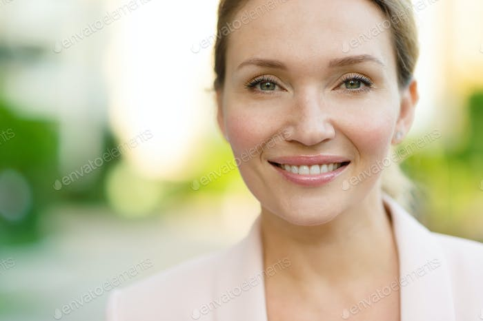 Close-up portrait of a smiling woman on the street.