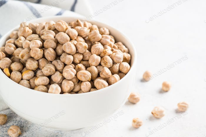 Chickpeas in white bowl at light kitchen table