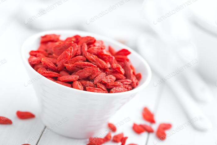 Goji berries in bowl on white background