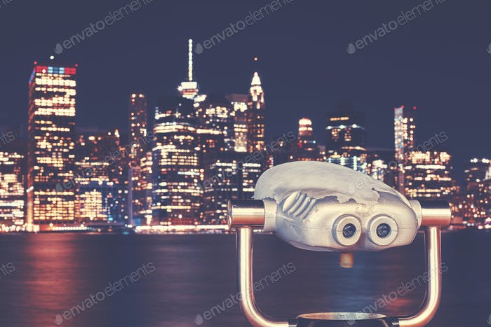Vintage toned binoculars with New Your skyline at night, USA.