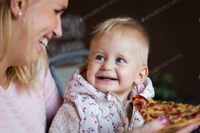 Lovely blond little baby girl in beautiful white dress biting on piece of tasty pizza