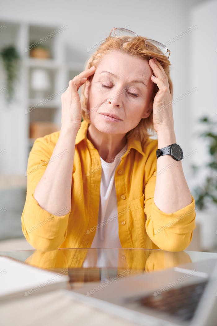 Tired mature businesswoman touching head while suffering from headache