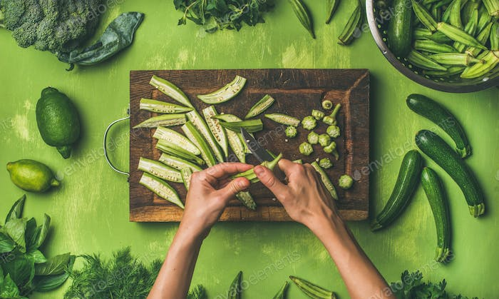 Flat-lay of healthy green vegan cooking ingredients over green background