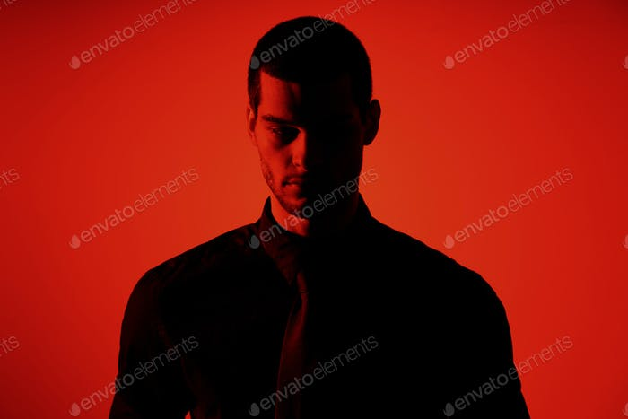 Silhouette of a young confident handsome businessman wearing black shirt in red light