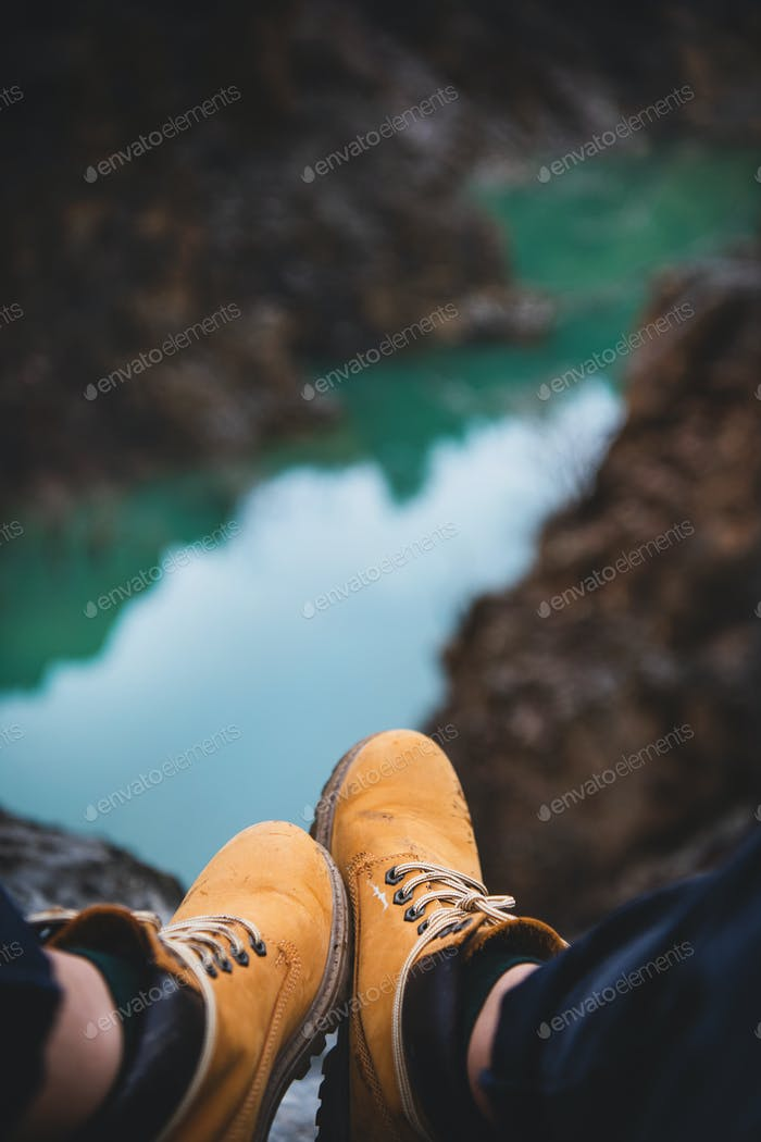 Feet of traveler in boots sitting over river canyon