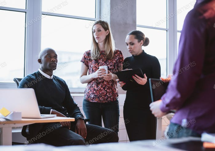 Business people having informal meeting in office